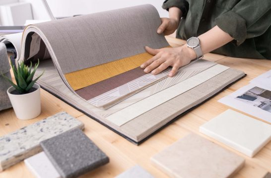 Hands of young designer of interior standing by table and choosing wallpapers for new order among panel samples